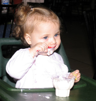 маленькая девочка облизывает ложку