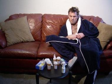 больной мужчина полулежит на диване перед столиком с лекарствами