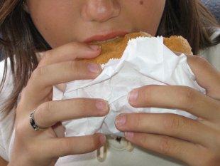 девушка держит в руках и ест жирный пирожок