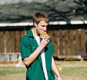 молодой человек идёт по улице и кушает кусок пиццы