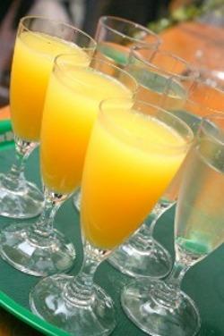 ряды бокалов апельсинового и виноградного сока