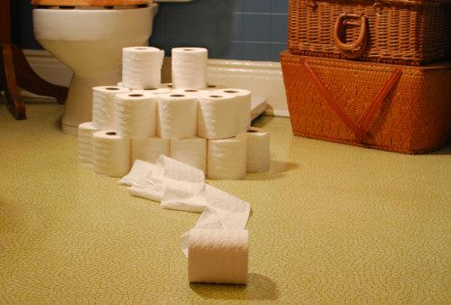 горка рулонов туалетной бумаги возле унитаза