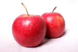 два спелых красных яблока на белом фоне