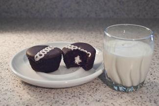 два шоколадных пирожных на тарелке и стакан молока