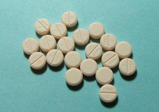 двадцать рассыпанных таблеток на голубом фоне