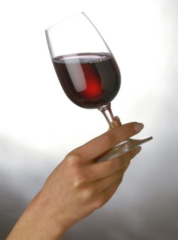 женская рука с бокалом красного вина
