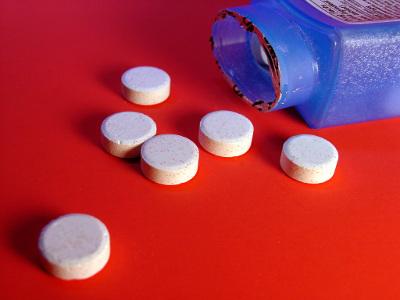 шесть рассыпанных белых таблеток на красном фоне