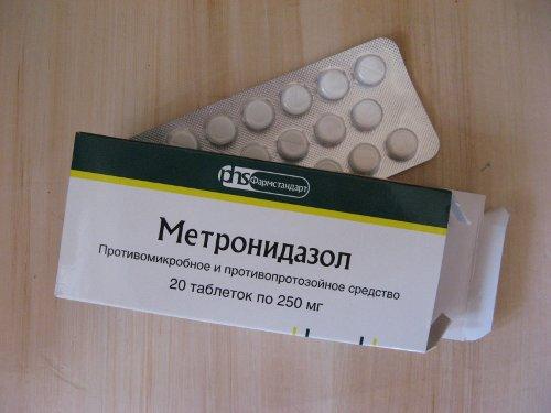 открытая упаковка метронидазола и блистер с таблетками рядом