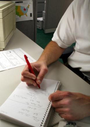 рука с ручкой над листом исписанной бумаги