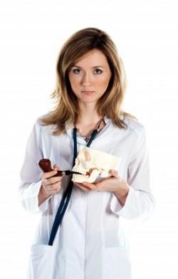 девушка-врач с черепом и курительной трубкой в руках