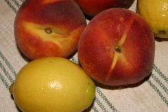 несколько крупных персиков и лимонов на скатерти
